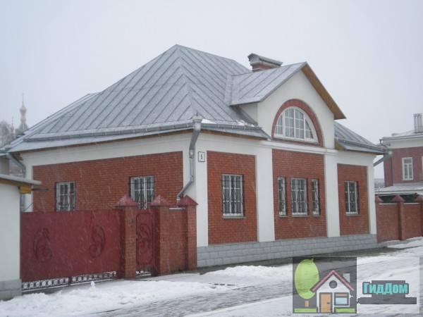 Вид вполоборота на дом №5 по улице Лазарева. Снимок сделан в светлое время суток при слабом снегопаде.