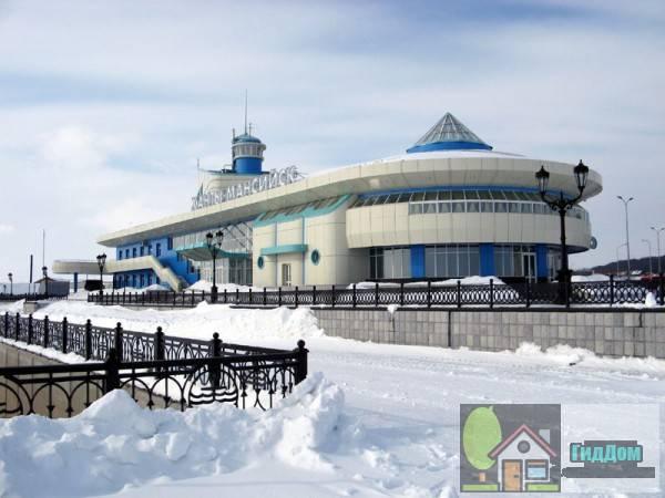 Вид на здание речного порта и автовокзала в Ханты-Мансийске, Россия. Снимок сделан в светлое время суток. Изображение загружено из Википедии.