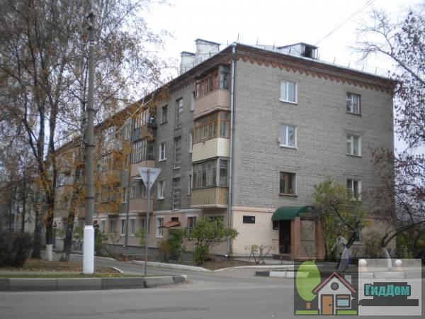 Вид вполоборота на многоквартирный жилой дом №16 по проспекту Кирова со стороны улицы Ленина с дворовой стороны. Снимок сделан в выходной день в светлое время суток при слабой облачности.