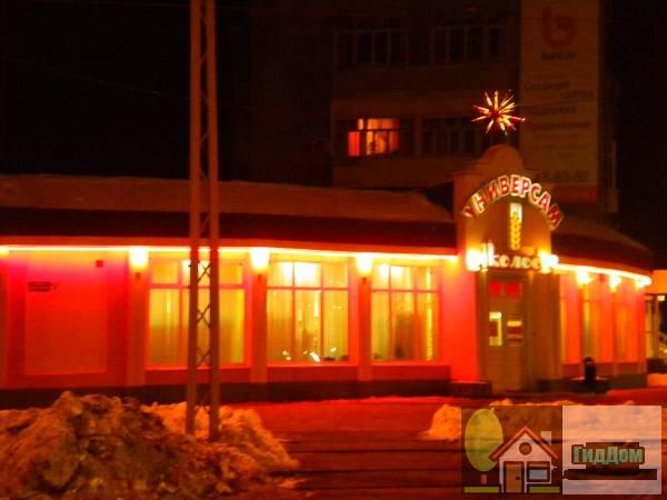 Вид вполоборота на здание продуктового магазина Колос на площади Советской (дом №5а по Советской площади) со стороны улицы Гагарина. Снимок сделан в выходной день в тёмное время суток при ясной погоде.