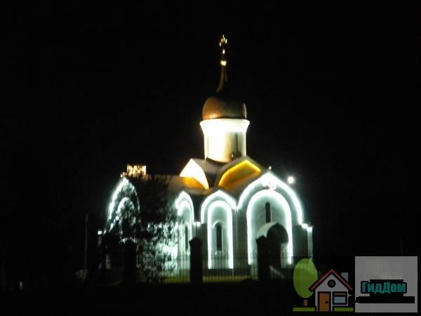 Вид спереди на церковь на въезде в посёлок Радужный. Снимок сделан в выходной день в тёмное время суток при слабой облачности.