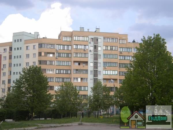 Вид спереди на многоэтажный жилой «Польский» дом №76 на улице Дзержинского с юго-западной стороны стороны. Снимок сделан в выходной день в светлое время суток при слабой облачности.