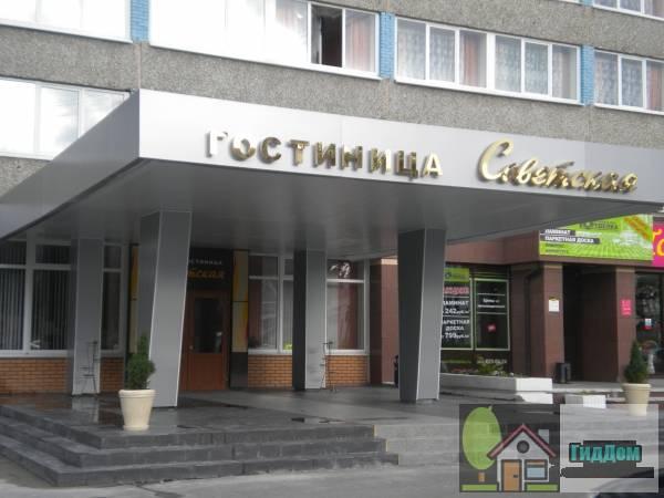 Вид спереди на главный вход гостиницы  «Советская» на проспекте Кирова с противоположной стороны проспекта с северо-западной стороны. Снимок сделан в выходной день в светлое время суток при слабой облачности.