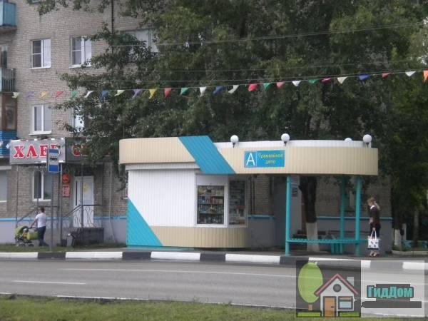 Вид вполоборота на автобусную остановку «Трамвайное управление» на проспекте Кирова с противоположной стороны проспекта северо-восточной стороны. Снимок сделан в выходной день в светлое время суток при сильной облачности.