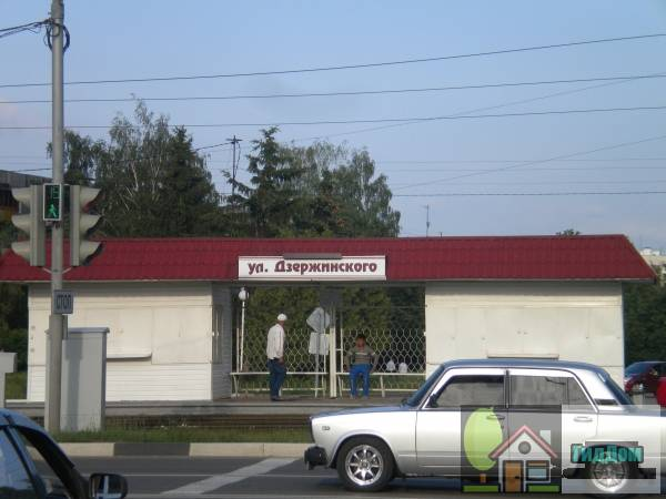 Вид спереди на трамвайную остановку «улица Дзержинского» на проспекте Кирова с противоположной стороны проспекта с западной стороны. Снимок сделан в выходной день в светлое время суток при ясной погоде.