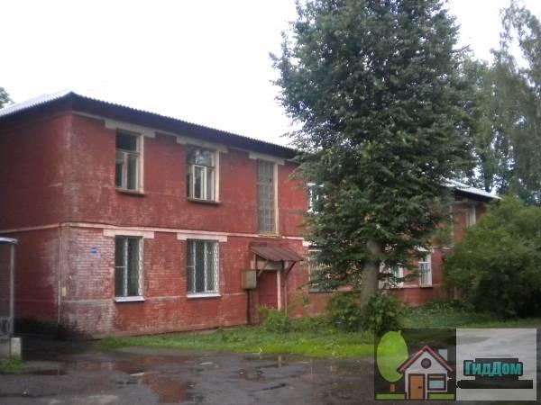 Вид вполоборота на малоэтажный жилой дом из красного кирпича (дом №288) по улице Октябрьской Революции с юго-западной стороны. Снимок сделан в выходной день в светлое время суток при сильной облачности после дождя.