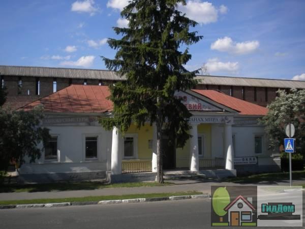 Вид спереди на здание гаупвахты на площади автовокзала на улице Зайцева с западной стороны. Снимок сделан в выходной день в светлое время суток при сильной облачности.