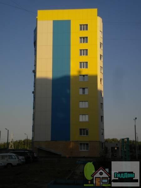 Вид с торца на желто-бело-синий панельный жилой дом №82 на проспекте Кирова с юго-восточной стороны. Снимок сделан в светлое время суток при слабой облачности.