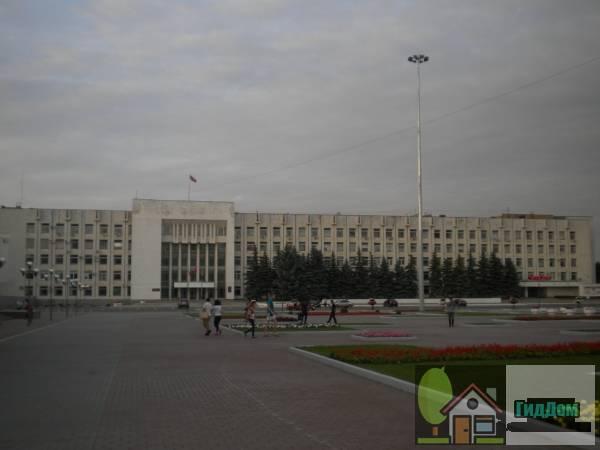 Вид вполоборота на здание коломенского «Белого дома» (дом №1) со стороны Советской площади с юго-западной стороны. Снимок сделан в светлое время суток при сильной облачности.