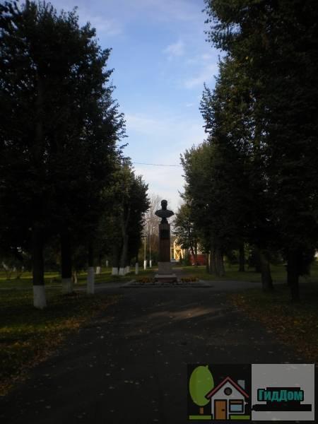 Вид на центральную аллею и бюст дважды Героя Советского Союза лётчика-истребителя В.А. Зайцева в сквере имени Зайцева в Коломне с южной стороны. Снимок сделан в светлое время суток при слабой облачности.