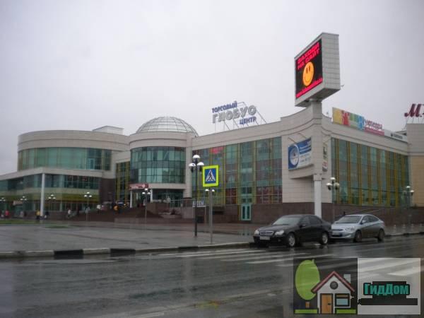 Вид вполоборота на здание торгового центра «Глобус» (дом №8) на Советской площади с северо-восточной стороны. Снимок сделан в светлое время суток при слабом дожде.