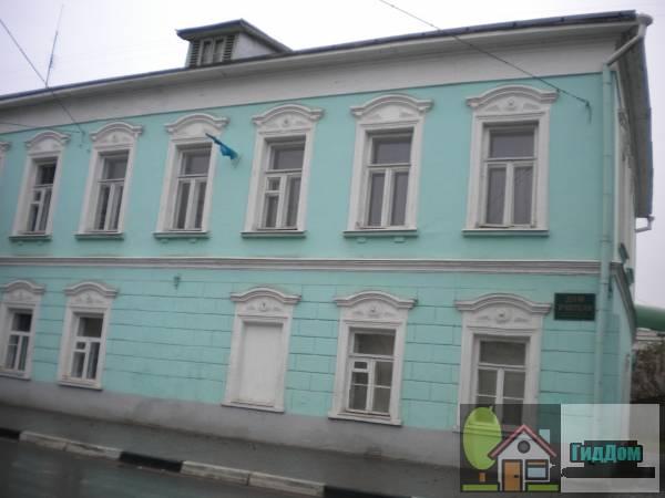 Вид вполоборота на Дом учителя (дом №232) на улице Октябрьской Революции с северо-восточной стороны. Снимок сделан в светлое время суток при слабом дожде.