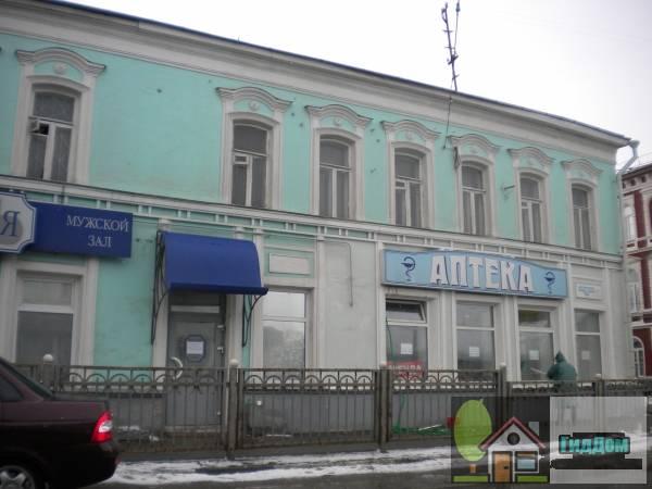 Вид вполоборота на двухэтажный жилой дом №202 с аптекой на первом этаже на улице Октябрьской Революции с северо-восточной стороны. Снимок сделан в светлое время суток при слабой облачности.