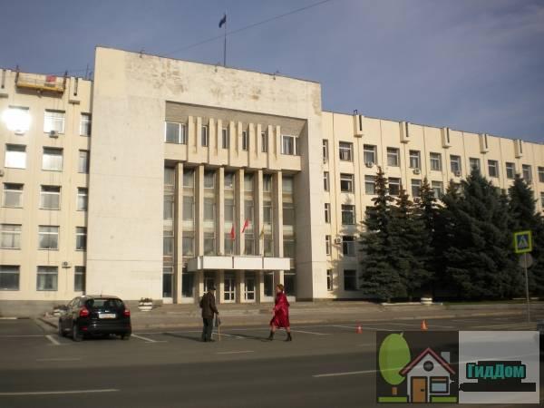 Вид вполоборота на здание городской администрации (дом №1) на Советской площади с юго-западной стороны. Снимок сделан в светлое время суток при слабой облачности.