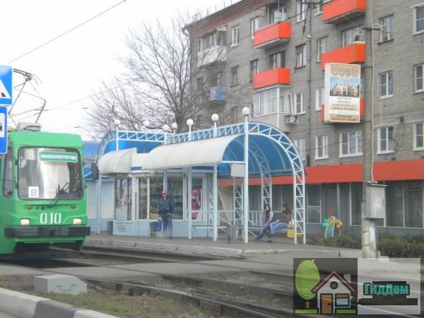 Вид вполоборота на павильон трамвайной остановки «площадь Советская» на Советской площади с юго-западной стороны во время прохождения трамвая 71-134К по 8-му маршруту. Снимок сделан в светлое время суток при сильной облачности.