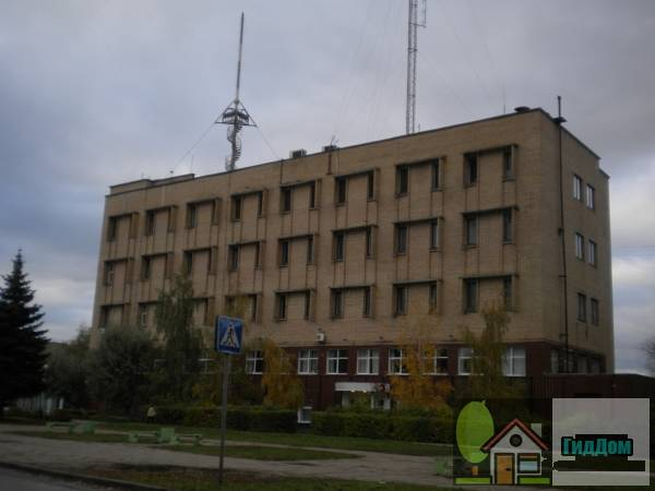Вид вполоборота на административный центр (дом №98) на улице Дзержинского с юго-восточной стороны. Снимок сделан в светлое время суток при сильной облачности.