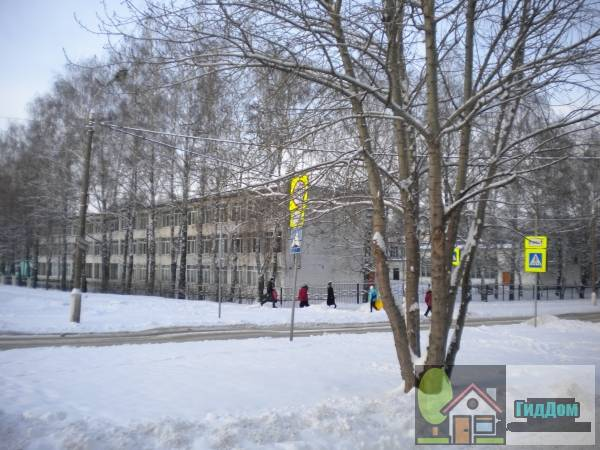 Вид вполоборота на здание общеобразовательной школы (дом №90) на углу улиц Дзержинского и Добролюбова с северо-восточной стороны. Снимок сделан в светлое время суток при сильной облачности.