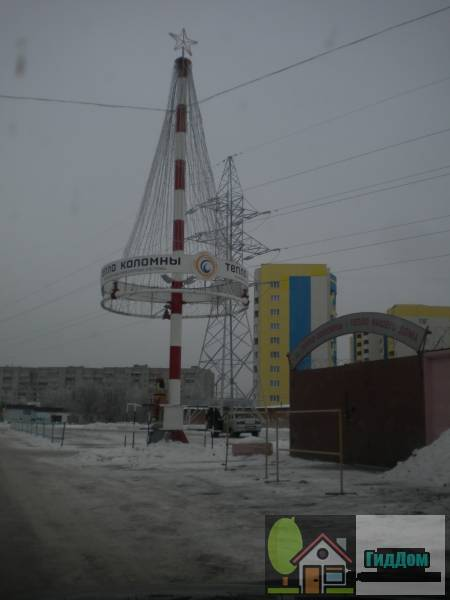 Вид вполоборота на стелу у здания компании «Тепло Коломны» (дом №64) на проспекте Кирова с северо-восточной стороны. Снимок сделан в светлое время суток при сильной облачности.