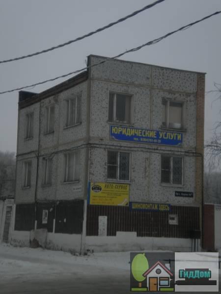 Вид вполоборота на административное панельное здание (дом №66) на проспекте Кирова с северо-восточной стороны. Снимок сделан в светлое время суток при сильной облачности.