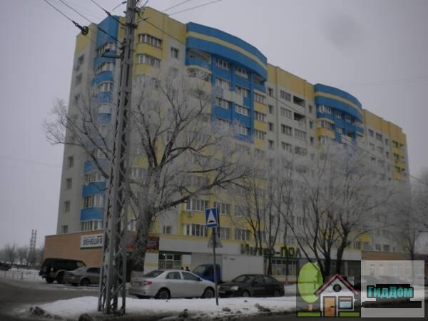 Вид вполоборота на панельный жилой дом №78 на проспекте Кирова с юго-восточной стороны. Снимок сделан в светлое время суток при сильной облачности.