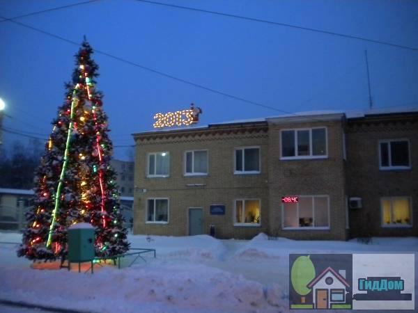 Вид вполоборота на здание трамвайного управления (дом №3) на проспекте Кирова во время Новогодних праздников с западной стороны. Снимок сделан в тёмное время суток при слабой облачности.