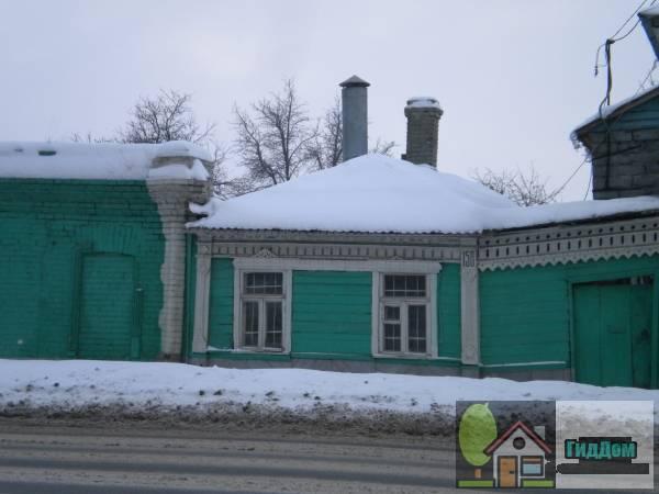 Вид вполоборота на флигель частного жилого дома №158 на высоком подклёте на улице Октябрьской Революции с северной стороны. Снимок сделан в светлое время суток при слабой облачности.