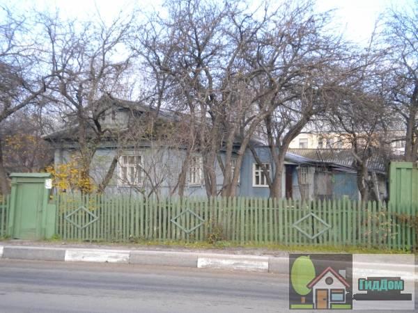 Вид вполоборота на деревянный частный жилой дом №427 в Голутвине на улице Октябрьской Революции с юго-восточной стороны. Снимок сделан в светлое время суток при слабой облачности.