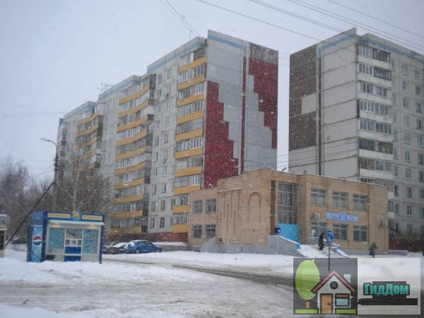 Вид вполоборота на панельный многоквартирный жилой дом №9/15 на пересечении улицы Спирина и бульвара 800-летия Коломны с северо-восточной стороны. Снимок сделан в  светлое время суток при сильном снегопаде.