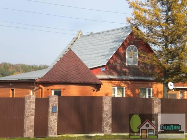 Вид вполоборота на частный жилой дом №32а из красного кирпича на центральной улице деревни Андреевки с западной стороны. Снимок сделан в  светлое время суток при слабой облачности.