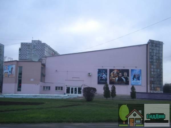 Вид вполоборота на здание кинотеатра «Горизонт» (дом №6) на Советской площади. Снимок сделан в светлое время суток при слабой облачности.