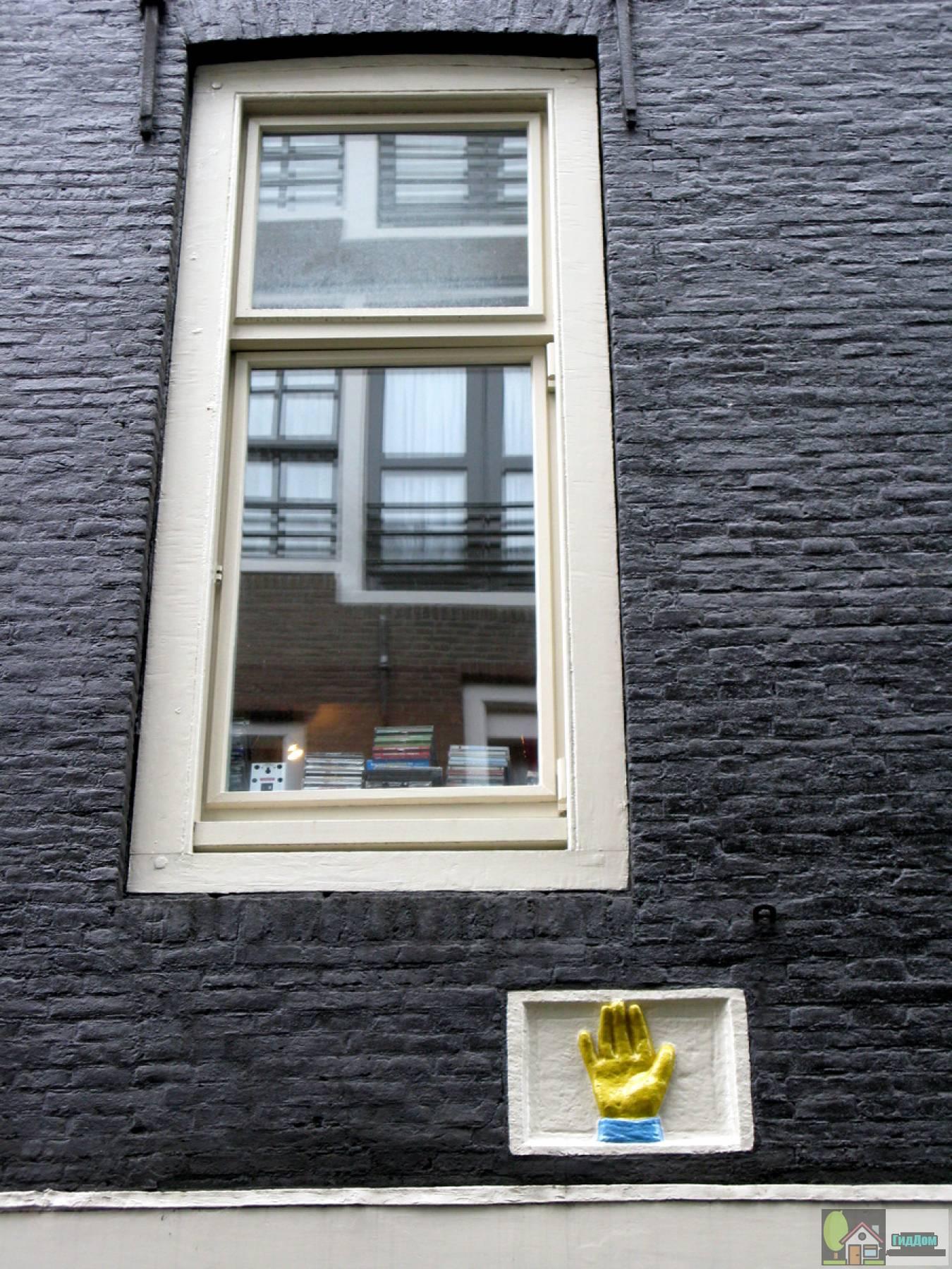 (Dubbel pakhuis met trapeziumgevels aan voor- en achterzijde beide met gevelsteen met hand, bij de laatste met een grote kroon erboven)