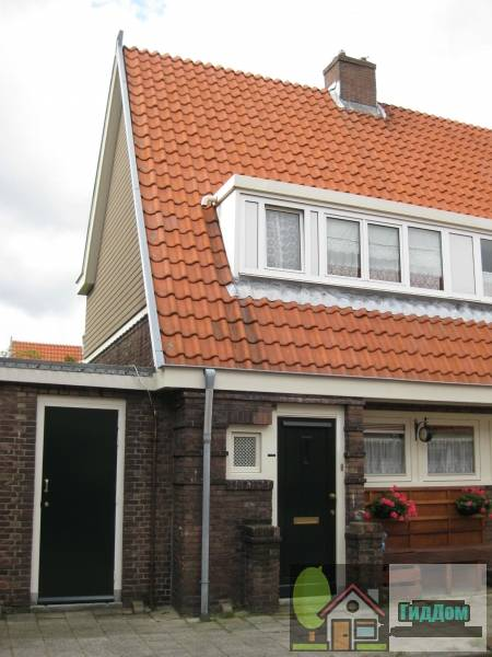 (Blok met 8 keukenwoningen, zo genoemd vanwege destijds nieuwe plaatsing van keuken aan de voorzijde, aan de zijkant een houten topgevel, bouwstijl Amsterdamse School, samen met de poortgebouw langs de Purmerweg centraa