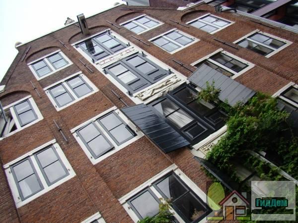 (Breed pakhuis met gevel onder trapeziumtop, voorzien van tweelichten in verticaal gekoppelde korfboognissen en gevelstenen tussen de ophaaldeuren)